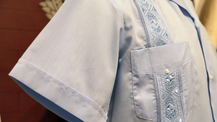 "In this Wednesday, Oct. 17, 2012 photo, a guayabera made in Mexico in 2012 featuring machine made embroidery, is on display at an exhibition titled ""The Guayabera: A Shirt's Story"" at the Museum of History Miami, in Miami. This is the first exhibition to trace the story of the shirt's evolution through Cuba, Mexico, and the United States. (AP Photo/Lynne Sladky)"