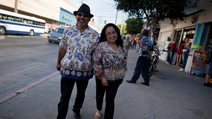 In this Friday, Jan. 27, 2012 photo, Agustin, left, and Ana Portillo walk through the streets of central Tijuana in Tijuana, Mexico.  Ana, a naturalized U.S. citizen who lives and works in Los Angeles, visits Agustin in Tijuana twice a month. The federal law that prohibits many illegal immigrants from living in the United States with their citizen spouses has been criticized by President Barack Obama, who proposed an overhaul that would allow some families to stay together. But it's unclear when the new policy will go into effect or how many families it will help. (AP Photo/Julie Jacobson)