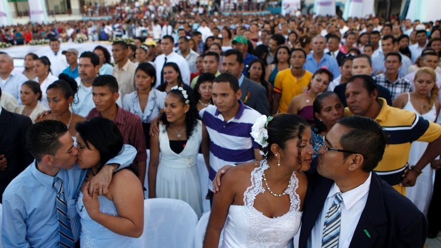 Couples participate in a mass wedding in Managua, Nicaragua, Thursday, Feb 14, 2013. A public square in Nicaragua has become an improvised wedding chapel for 550 couples who took their marriage vows on Valentine's Day in a mass wedding. Mass weddings have become a tradition in the Nicaraguan capital of Managua since they began a decade ago. (AP Photo/Esteban Felix)