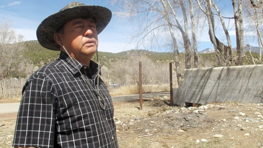 In this March 26, 2013 photo, Arroyo Hondo Land Grant heir Fernando Martinez is shown at the historical northern New Mexico Spanish land grant. Some heirs and homeowners currently are locked in a dispute after a land grant board filed a warranty deed in an attempt to reclaim 20,000 acres of private land originally granted by Spain's colonial government to Arroyo Hondo's founding families. The fight is preventing property owners like Martinez from selling property, refinancing mortgages, or getting insurance policies while the courts struggle to unravel the conflict.  (AP Photo/Russell Contreras)