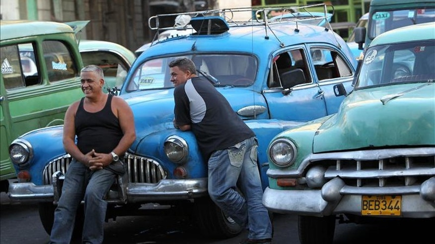Two taxi drivers chat next to their cabs while waiting for passengers in Havana, where for the first time in decades they face the unusual situation of having to compete for passengers.