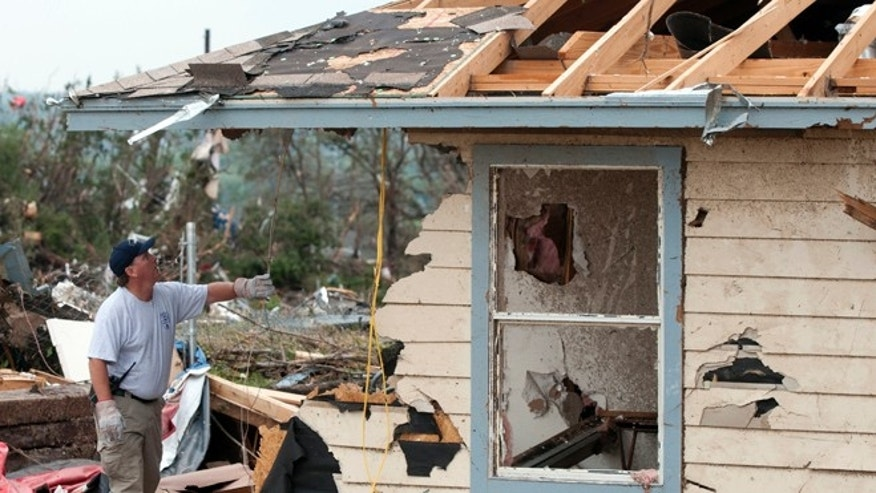 A police officer looks through debris near Granbury, Texas on Thursday, May 16, 2013. Ten tornadoes touched down in several small communities in Texas overnight, leaving at least six people dead, dozens injured and hundreds homeless. Emergency responders were still searching for missing people Thursday afternoon. (AP Photo/Rex C. Curry)