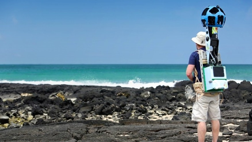 In this May 2013 photo provided by Google, Daniel Orellana of the Charles Darwin Foundation collects seashore imagery with the Street View Trekker at the Los Humedales wetland area on Isabela Island in the Galapagos. Few have laid eyes on many of the volcanic islands of the Galapagos archipelago that remain closed to tourists. But soon the curious will be able to explore these places that inspired Charles Darwin's theory of evolution from their computers or mobile devices. Google Maps sent crews armed with backpack-mounted Street View cameras and underwater gear to the Galapagos, and will be bringing the islands' natural wonders to the Internet. (AP Photo/Google)