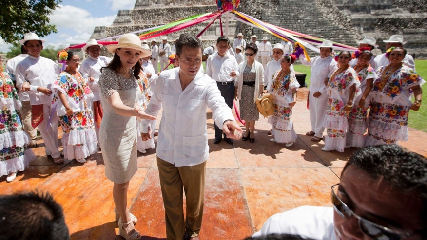 Mexico's President Enrique Pena and his wife Angelica Rivera instruct their security detail to allow access to China's presidential photographer, as they prepare for a group photo with Chinese President Xi Jinping, and his wife Peng Liyuan, near the Mayan ruins of Chichen Itza, southern Mexico, Thursday, June 6, 2013. Xi is on the final day of his 3-day visit to Mexico. The two presidents agreed to broaden relations between their countries and expand trade ties, including opening the Chinese market to imports of Mexican tequila and pork. (AP Photo/Eduardo Verdugo)