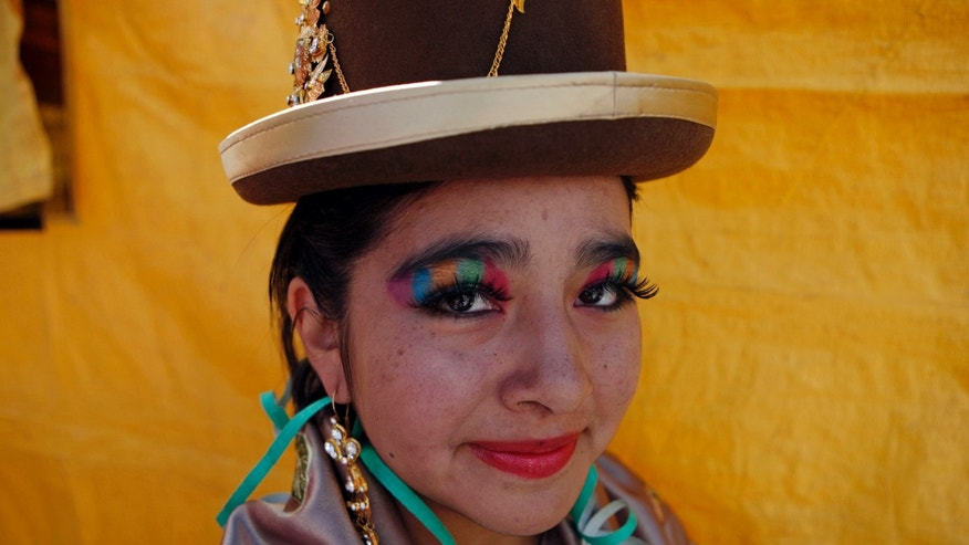 An Aymara dancer poses for photos after performing at the Miss Cholita 2013 beauty pageant in La Paz, Bolivia, Sunday, June 30, 2013. Cholita is the style of clothing worn by many of the country's indigenous women. (AP Photo/Juan Karita)