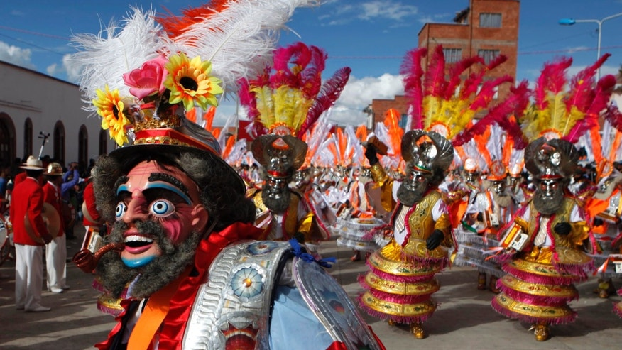 In this July 19, 2013 photo, masked dancers parade through the streets during a festival held in honor of Santiago the apostle, known as Saint James in English, the patron saint of the town in Guaqui, Bolivia. In the Bolivian highlands along the shores of Lake Titicaca, this Aymara Indian community celebrates St. James the weekend before his feast day on July 25. (AP Photo/Juan Karita)