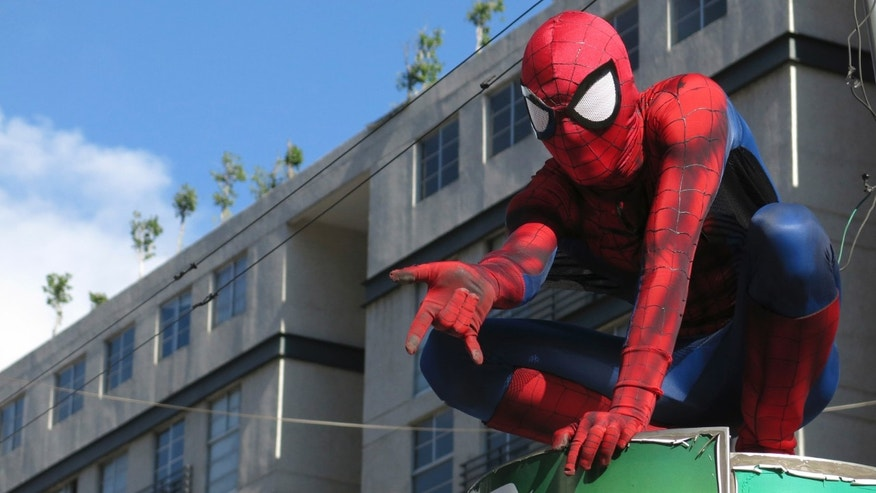 In this July 27, 2013 photo, a man dressed as comic superhero Spiderman strikes a pose for fans outside the building hosting La Mole Comic-Con Internacional in Mexico City. Like the character created by Stan Lee in 1962, he climbed to the top of a battery recycling station outside the convention. (AP Photo/Isaac Garrido)