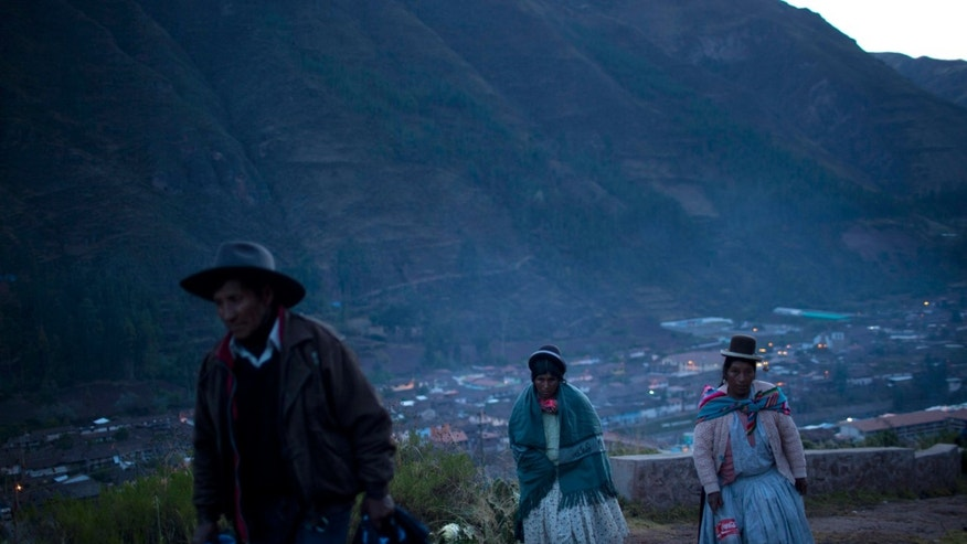 In this Sept. 14, 2013 photo, pilgrims walk towards the Lord of Huanca in Cuzco, Peru. Devotees from across Peru and neighboring countries come to Cuzco to make the annual seven-hour night hike to the mountain, to honor a 339-year-old image of Christ scourged and bleeding, known as the Lord of Huanca, on the walls of the shrine. The 3-day celebration beginning on the eve of Sept. 14, attracts thousands of people carrying candles and flowers to the shrine, which is also accessible by vehicle. (AP Photo/Rodrigo Abd)