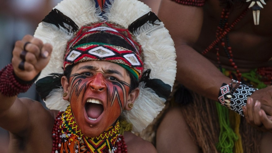 "A Pataxo Indian celebrates after his tribe defeated their competitors in a tug of war competition during the 12th Indigenous Games in Cuiaba, Brazil, Thursday, Nov. 14, 2013. More than 1,500 participants from 48 Brazilian tribes, as well as from more than a dozen other nations, descended this week on Cuiaba, the capital of Mato Grosso state, for the games that end Saturday. All participants will earn ""medals"" carved from wood, seeds and other natural items. (AP Photo/Felipe Dana)"