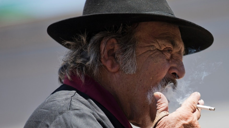 "Alberto Lastre smokes outside a bar after parading on ""Tradition Day"" in San Antonio de Areco, Argentina, Sunday, Nov. 17, 2013. This town in Buenos Aires province holds a gaucho festival every year to honor the birth of Argentine writer Jose Hernandez, author of the country's national poem ""The Gaucho Martin Fierro,"" about the Argentine gaucho lifestyle. People from across the country attend the celebration to preserve gaucho traditions. (AP Photo/Natacha Pisarenko)"