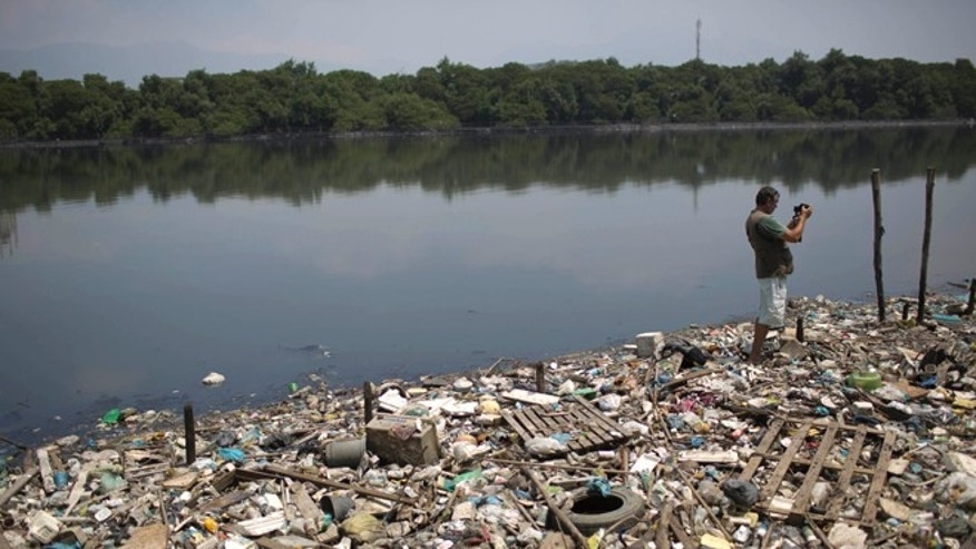 In this Oct. 23, 2013 photo, biologist Mario Moscatelli takes photographs from trash floating on the polluted waters of the Canal do Fundao in Rio de Janeiro, Brazil. Moscatelli, who oversees the reforestation of mangrove forests along the bay, said he fears that even if the bay is cleaned up, the state will let it deteriorate after all the athletes have gone home. Rio de Janeiro will host the 2016 Olympic Games. (AP Photo/Felipe Dana)