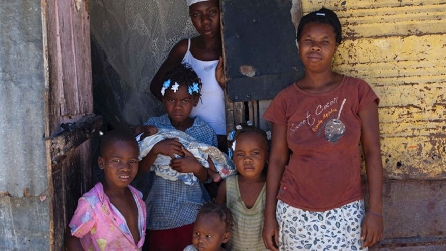 In this Nov. 12, 2013 photo, Nathalie Berjean, 32, right, poses for a photo with her five children and her cousin in front of their home in Jimani, Dominican Republic, near the border with Haiti. In September, the Dominican Constitutional Court ruled that being born in the country does not automatically grant citizenship, and it directed officials to purge voter rolls of non-citizens, including people born to non-legal residents going back to 1929.  (AP Photo/Dieu Nalio Chery)