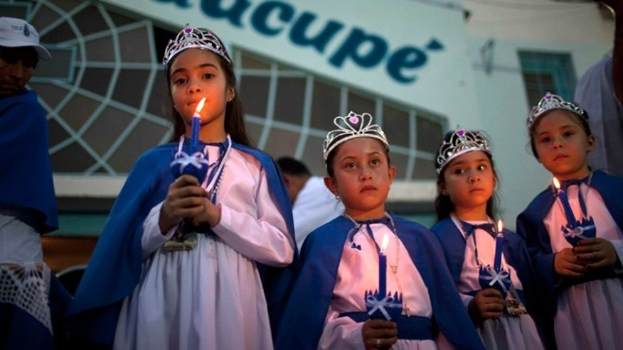 "In this Dec. 8, 2013 photo, girls dressed in the likeness of Paraguay's patroness, ""Our Lady of Caacupe,"" commonly called the ""Blue Virgin"" hold lit candles before the start of a Mass in a slum in Buenos Aires, Argentina. The slum's parish is named for Paraguay's patroness by the half-million Paraguayans who migrated to Argentina, many of whom live in ramshackle settlements known as ""misery villages"" in and around Buenos Aires. (AP Photo/Rodrigo Abd)"