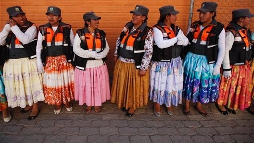 In this Nov. 28, 2013 photo, Aymara women traffic cops speak during a training session before heading out to control the vehicular traffic on the streets of El Alto, Bolivia. The Bolivian highlands' city has hired Aymara women dressed in traditional multi-layered Andean skirts and brightly embroidered vests to work as traffic cops and bring order to its road chaos. (AP Photo/Juan Karita)