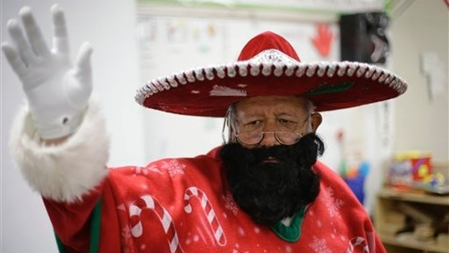 In this Friday, Dec. 20, 2013, photo, Pancho Claus, Rudy Martinez, waves to children as he visits Knowlton Elementary School, in San Antonio. Pancho Claus, a Tex-Mex Santa borne from the Chicano civil rights movement in the late 1970s and early 1980s, is now an adored Christmas fixture in many Texas cities. (AP Photo/Eric Gay)