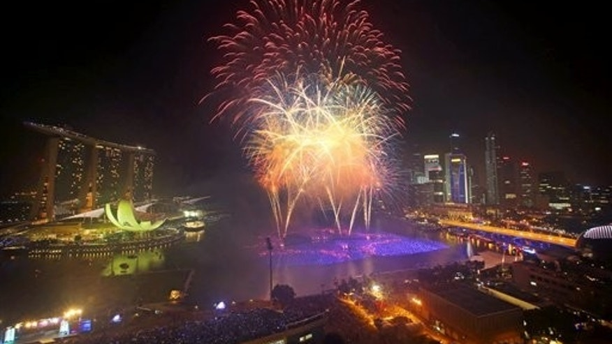Fireworks explode over the financial district at midnight, Wednesday, Jan. 1, 2014 in Singapore. Celebrations started on New Year's Eve where concerts were held and thousands gathered on the streets to usher in the Year 2014. (AP Photo/Wong Maye-E)
