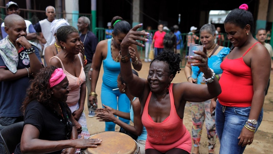 Dionisia Imeli Rosendo, 60, dances during a ceremony honoring Eshu-Elegbara, the deity associated with markets and commerce, and protector of the universe at the Cuatro Caminos market in Havana, Cuba, Monday, Dec. 30, 2013. Cuban followers of the Santeria faith gathered at Havana's most important market to sing ceremonial songs in the Yoruba language and spit rum at a 2-foot-tall statue of Eshu-Elegbara, to give thanks for the year's blessings and ask for prosperity in 2014. (AP Photo/Franklin Reyes)