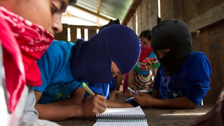 "In this Dec.  27, 2013 photo, children study at a school in the Zapatista controlled community of La Garrucha, Mexico. In these communities, children attend schools called ""Sun Seeds"" where they learn to read and write and study about nature conservancy and the environment. They also learn how to be productive members of their communities, and more importantly, how to protect the autonomy of their communities. Members of these communities wear masks to hide their identities when outsiders, interested in learning about how they self-govern and maintain their way of life, gain access to visit them. (AP Photo/Christian Palma)"