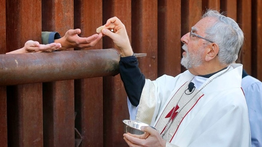 Most Reverend Gerald F. Kicanas, Bishop of Tucson, offers communion to people on the Mexican side of the international border, Tuesday, April 1, 2014, in Nogales, Ariz. Kicanas and Boston Archdiocese Cardinal Sean O'Malley, along with several Bishops who serve along the U.S./Mexico border, were visiting the border town to bring awareness to immigration reform and to remember those who have died trying to cross the border in years past. (AP Photo/Matt York)