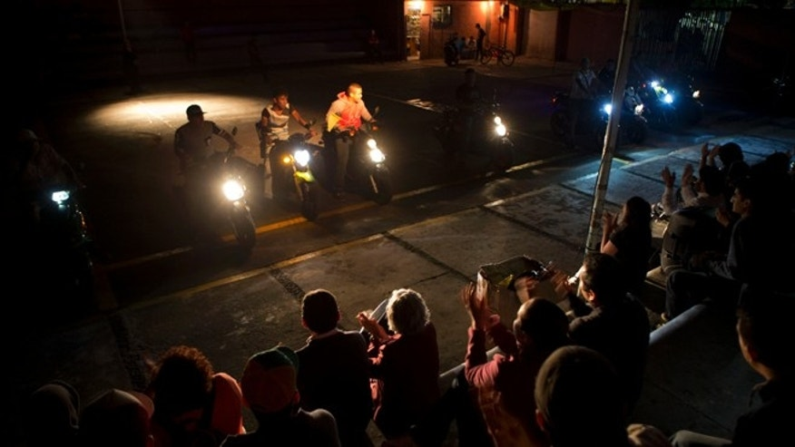 "In this April 11, 2014 photo, visitors applaud as motorcycle drivers from Tepito perform a synchronized ride at the conclusion of a theater project showcasing the lives of residents of the troubled neighborhood in Mexico City. The project, titled ""Safari in Tepito"" has provided employment for some residents, such as the motorcycle drivers. (AP Photo/Rebecca Blackwell)"