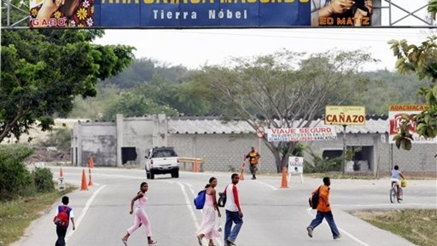 "FILE - In this Jan. 4, 2006 file photo, people pass under a billboard that reads in Spanish ""Welcome to the magical world of Macondo"" decorated with images of Colombian Nobel laureate Gabriel Garcia Marquez at the entrance of Marquez's hometown of Aracataca, Colombia. Marquez died on Thursday, April 17, 2014 at his home in Mexico City.  (AP Photo/Fernando Vergara, File)"
