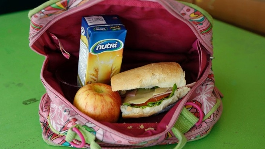 A student's lunch box brought from home sits on display at an elementary school in Quito, Ecuador, Tuesday, May 6, 2014. The lunch consists of a sandwich of ham, cheese, tomato and lettuce, a boxed oatmeal drink, and an apple. (AP Photo/Dolores Ochoa)