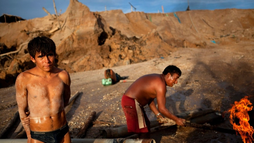 In this May 4, 2014 photo, a miner stands next to a tube used to transport soil removed from a surrounding crater to a sluice-like carpeted contraption to filter gold in La Pampa in Peru's Madre de Dios region. Artisanal gold miners began carving the lawless, series of ramshackle settlement out of Amazon jungle in 2008. The miners who are working up to the last minute, know they will be soon be evicted, Peru's government declared all informal mining illegal on April 19. (AP Photo/Rodrigo Abd)