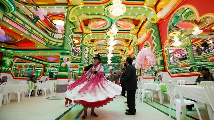 In this May 17, 2014 photo, an Aymara woman dances in a ballroom of one of the newfangled mini-mansions rising up in El Alto, Bolivia. They attest to a new class of indigenous nouveau riche, many of them merchants who converted street stalls into fortunes. Owners often sink a million dollars into the opulent edifices.  (AP Photo/Juan Karita)