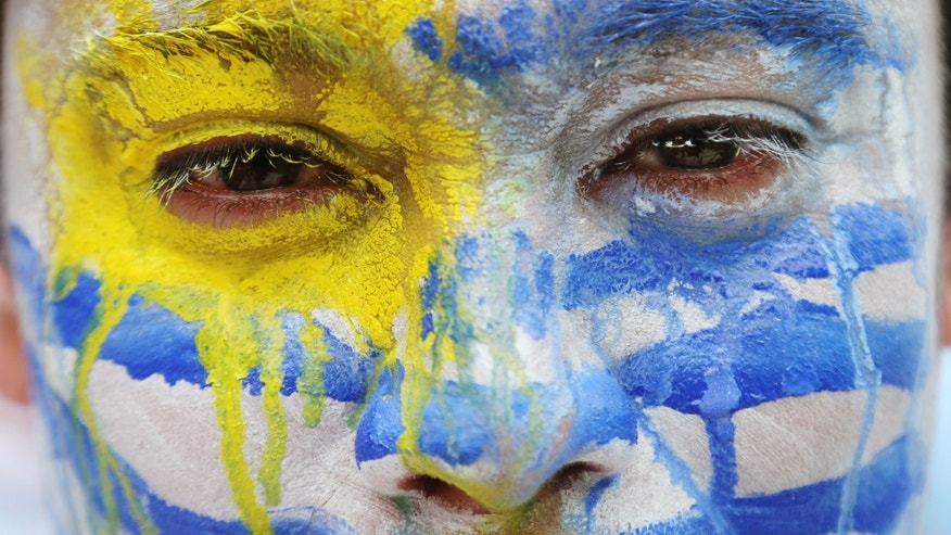 An Uruguay soccer fan wears face paint before the group D World Cup soccer match between Italy and Uruguay at the Arena das Dunas in Natal, Brazil, Tuesday, June 24, 2014. (AP Photo/Petr David Josek)