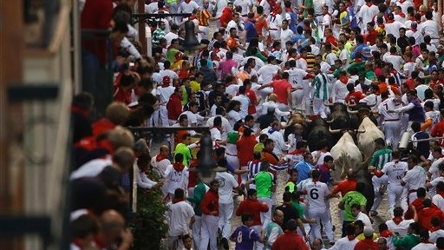 Jandilla fighting bulls run in between revelers during the running of the bulls at the San Fermin festival, in Pamplona, Spain, Friday, July 11, 2014. Revelers from around the world arrive to Pamplona every year to take part in some of the eight days of the running of the bulls. (AP Photo/Andres Kudacki)
