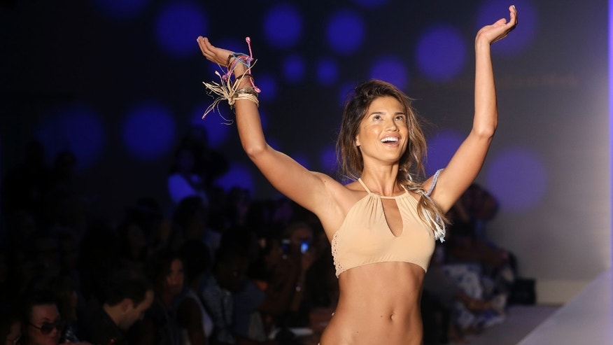 A model walks down the runway wearing swimwear designed by Frankie's Bikinis during the Mercedes-Benz Fashion Week Swim show, Friday, July 18, 2014, in Miami Beach, Fla. (AP Photo/Lynne Sladky)