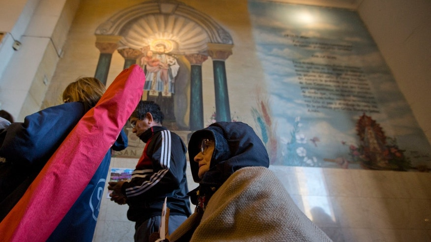 A woman kneels as she enters San Cayetano church in Buenos Aires, Argentina, Thursday, Aug. 7, 2014. Pilgrims flock to show their dedication to the saint widely known as 'San Ca' – the patron of labour – and ask for three things in particular: Bread, work and peace. (AP Photo/Natacha Pisarenko)