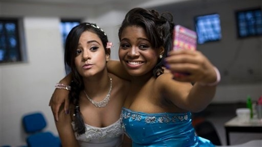"Jaqueline, right, and Monique take a selfie before their debutante ball organized by the Pacifying Police Unit from their neighborhood, the Santa Marta ""favela"" slum, in Rio de Janeiro, Brazil, Friday, Aug. 29, 2014. Fifteen-year-olds from Santa Marta made their coming out Friday night, escorted by police officers who patrol their communities. (AP Photo/Silvia Izquierdo)"