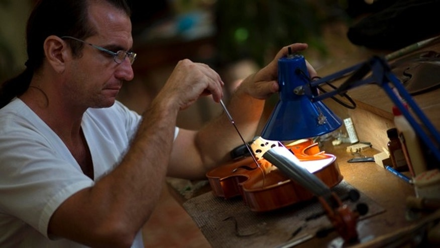 In this Oct. 14, 2014 photo, Andres Martinez repairs a viola at the Luthier Workshop of Havana, a state-run workshop where craftsmen make and repair violas, chelos and violins in Havana, Cuba. Martinez and his apprentices repair dozens of instruments a year, make a handful from scratch and train aspiring young fiddle-makers in an attempt to create an indigenous Cuban violin industry. (AP Photo/Ramon Espinosa)