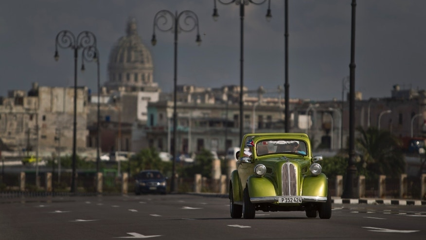 In this Oct. 15, 2014 photo, a man drives a classic American car on The Malecon in Havana, Cuba. This classic still running on the streets of Havana is part of a fleet of classic cars that have become an icon of tourism in the socialist nation. (AP Photo/Franklin Reyes)