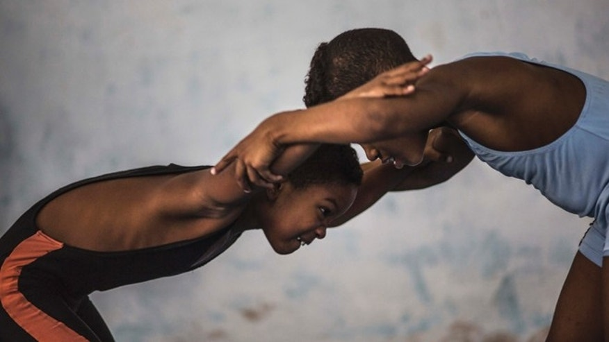 "In this Oct. 18, 2014 photo, two young wrestlers compete during a practice session during a training session in an auxiliary gym, in Old Havana, Cuba. About 20 children are learning to wrestle under the watchful eye of former wrestler Michael Guerra. When asked why they chose wrestling in baseball-loving Cuba, they shout in unison: ""To be like Mijain Lopez!"" Lopez has won two Olympic gold medals in Greco-Roman wrestling, as well as five world championships, and is one of Cuba's most heralded and popular athletes. (AP Photo/Ramon Espinosa)"