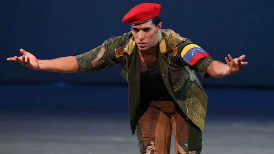 "John Lobo, 29, performing as Venezuela's late president Hugo Chavez, performs in the star role of the ""Ballet of the Spider-Seller to Liberator"", at the Teresa Carreno Theater in Caracas, Venezuela, Thursday, Nov. 27, 2014. Venezuela has found yet another way to honor the late leader who launched Venezuela's socialist revolution 15 years ago. A state-sponsored ballet about his life premieres, with dozens of performers recounting Chavez's life, from humble roots, to failed coup, to international fame. (AP Photo/Ariana Cubillos)"