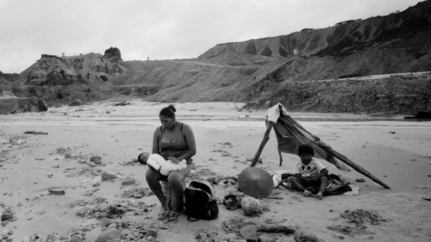 In this May 21, 2014 photo, Nilda Macedo holds her two-month-old baby Snyder not far from where her husband Joel mines for gold in Huepetuhe in the Madre de Dios region of Peru. Life is cheap in the mining camps. Deaths go unrecorded and the mercury miners use to bind the gold compounds the risks. Tons of mercury dumped into the environment poisons the food chain for society at large, starting with the miners and their families. (AP Photo/Rodrigo Abd)
