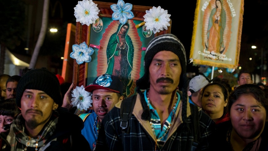Pilgrims carrying images of the Virgin of Guadalupe wait to be allowed into the Basilica of Guadalupe in Mexico City, Friday, Dec. 12, 2014. Every year hundreds of thousands of people from across the country, many carrying images or statues of Mexico's patron saint to be blessed, converge at the Basilica on Dec. 12, the Virgin's feast day. (AP Photo/Rebecca Blackwell)