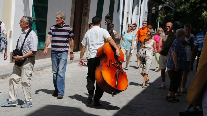 In this March 17, 2015 photo a musician carries his bass on a street crowded with tourists, in Havana, Cuba. Where foreigners see charming, historic architecture, bright 1950s-era American cars and vast stretches of white-sand beaches, locals see decaying buildings in need of repair, new vehicles priced beyond their reach and a lack of economic opportunity. (AP Photo/Desmond Boylan)