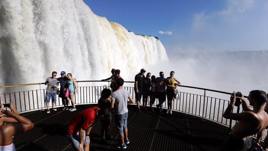 In this March 14, 2015 photo, tourists take pictures from a viewing area at Iguazu Falls in Brazil. From walkways and bridges, viewers can count 270 water falls almost 100 meters (330 feet) high. (AP Photo/Jorge Saenz)