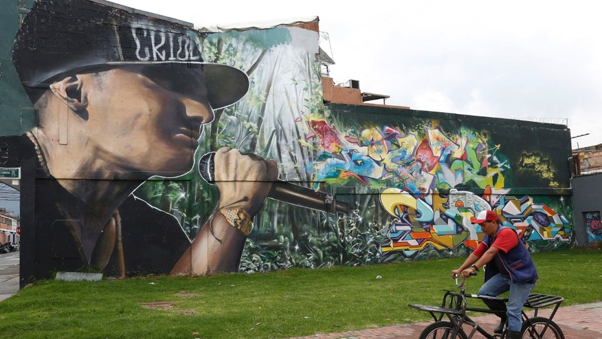 In this March 18, 2015 photo, a man rides past a wall painted by street artists, in Bogota, Colombia. Street art has subsequently exploded across the city of 8 million. By one count, there are now more than 5,000 large paintings on walls or the sides of buildings, many now well-known to the tourists who sign up for guided graffiti tours on bicycle.(AP Photo/Fernando Vergara)