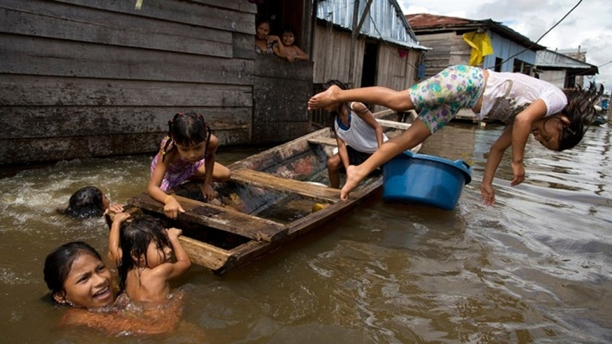 "In this April 19, 2015 photo, children play on a boat in the water outside their homes in the Belen neighborhood of Iquitos, Peru. This impoverished Peruvian Amazon community nicknamed ""Venice of the Jungle"" lives half the year on the water, with canoes replacing motorcycle taxis as the most popular form of transport. (AP Photo/Rodrigo Abd)"