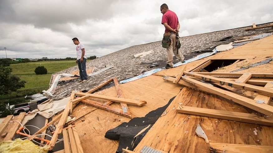 Edgar Mascorro, left, and Emir Nevarez check out the damage on the rooftop at the Silver Springs Apartments in North Austin, Texas, Sunday, May 24, 2015. Record rainfall was wreaking havoc across a swath of the U.S. Midwest on Sunday, causing flash floods in normally dry riverbeds, spawning tornadoes and forcing at least 2,000 people to flee. (Ricardo B. Brazziell/Austin American-Statesman via AP)  AUSTIN CHRONICLE OUT, COMMUNITY IMPACT OUT, INTERNET AND TV MUST CREDIT PHOTOGRAPHER AND STATESMAN.COM, MAGS OUT