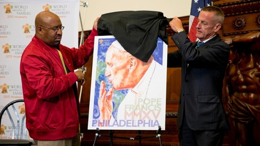 Philadelphia Mayor Michael Nutter, left, and Aramark CEO Eric Foss unveil artwork of Pope Francis by Perry Milou during a news conference, Monday, June 1, 2015, in Philadelphia. Aramark has been named the official retail provider of event merchandise for the scheduled Eighth World Meeting of Families Congress and Papal Visit to Philadelphia in September. (AP Photo/Matt Rourke)