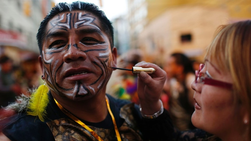 "In this May 30, 2015 photo, a woman paints the face of dancer before participating in the traditional ""Fiesta del Senor del Gran Poder"" or ""The Feast of the Lord of Great Power"" in La Paz, Bolivia. Today, the weeklong celebration is the city's largest festival and a major showcase of Andean folklore. (AP Photo/Juan Karita)"