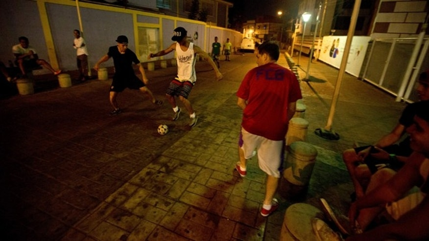 In this Wednesday, April 15, 2015 photo, youths play street soccer in the Petare shantytown in Caracas, Venezuela. As daylight fades in Caracas, packs of cyclists, groups of fitness-enthusiasts and families of film fans are coming out to reclaim their streets and parks from criminal gangs. (AP Photo/Fernando Llano)