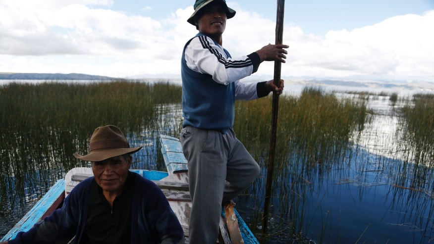 This April 25, 2015 photo shows fishermen pushing a boat with a pole on Lake Titicaca in Pata Patani, Bolivia. While only a small portion of Titicaca's waters are polluted, the affected areas are along shores where more than a half-million Aymara people live, according to lake authority president Alredo Mamani. (AP Photo/Juan Karita)