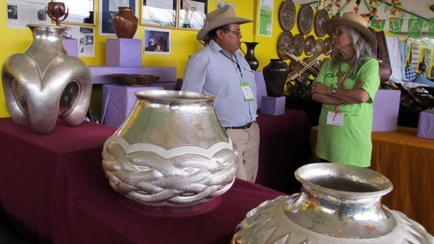 In this photo taken Saturday, July 11, 2015, decorative silver bowls and vases, created by a family of artists from Michoacan, Mexico, are displayed at the 12th annual International Folk Art Market in Santa Fe, N.M. The market draws close to 20,000 people and dozens of artists from around the globe over three days. (AP Photo/Susan Montoya Bryan)