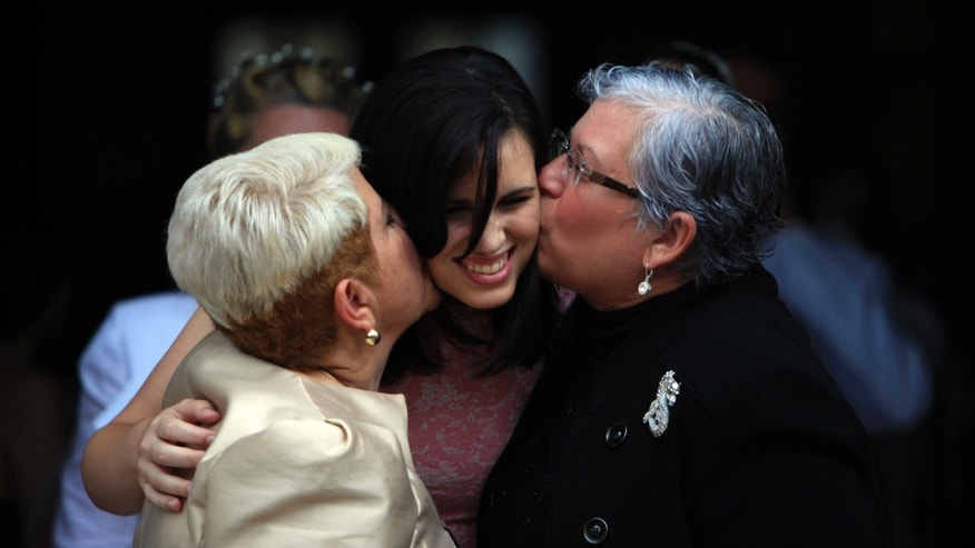 Ada Conde, right, and Ivonne Alvarez, left, kiss their daughter Adita Alvarez during a mass same-sex wedding in San Juan, Puerto Rico, Sunday, Aug. 16, 2015. Over 60 couples from around the region gathered in Puerto Rico's capital to exchange vows at a same-sex marriage ceremony. (AP Photo/Ricardo Arduengo)